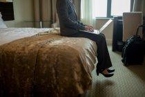 Деловая женщина с ноутбуком на кровати в номере отеля — стоковое фото