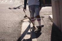 Низький розділ про людину, стоячи з скейтборд на тротуарі на вулиці — стокове фото