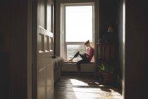 Mulher lendo livro no peitoril da janela em casa — Fotografia de Stock