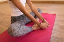 Faible section de femme effectuant des exercices de yoga dans le club de fitness — Photo de stock