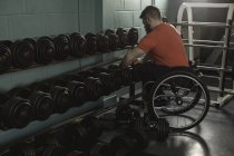 Handicapped man on wheelchair lifting dumbbell from rack in gym — Stock Photo