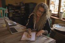 Mulher madura sentada na cadeira e escrevendo em papel em casa — Fotografia de Stock