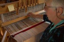 Активних старшим жінка ткацтва з шовку в магазин — стокове фото