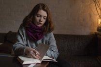 Femme note d'écriture sur le journal intime dans le salon à la maison — Photo de stock