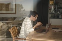 Young woman eating breakfast while looking into laptop in living room at home — Stock Photo