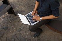 Sección media del hombre usando el ordenador portátil en la cafetería del pavimento - foto de stock