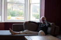 Старший разговаривает по мобильному телефону в гостиной на дому — стоковое фото