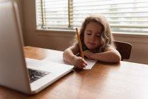 Mädchen schreibt zu Hause mit Bleistift auf ein Blatt Papier — Stockfoto