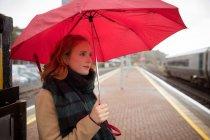 Jovem mulher com guarda-chuva, esperando o trem na plataforma — Fotografia de Stock