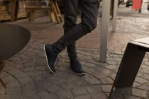 Faible section de casual homme debout en pavement café — Photo de stock