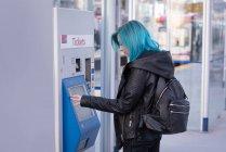 Femme élégante, à l'aide de distributeur automatique de billet à la gare — Photo de stock