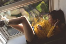 Donna che utilizza il telefono cellulare vicino alla finestra a casa — Foto stock