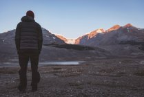 Rear view of man looking at snow capped mountains — Stock Photo