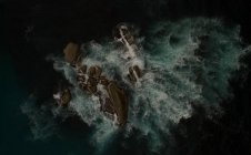 Aerial view of rocky island in dark sea water. — Stock Photo