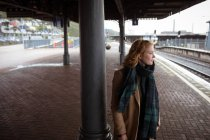 Curious young woman waiting for train at train platform — Stock Photo