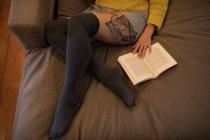 Mulher lendo livro enquanto relaxa no sofá em casa. — Fotografia de Stock