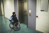 Behinderter Mann mit Rucksack im Rollstuhl wartet im Haus auf Aufzug — Stockfoto