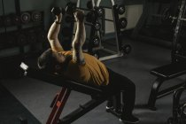 Handicapped man lifting dumbbells on bench in gym — Stock Photo