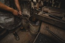 Blacksmith dipping hot metal rod in water at workshop — Stock Photo