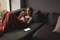 Молодая женщина пользуется мобильным телефоном дома — стоковое фото