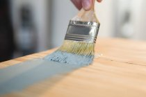 Close-up of male carpenter painting a table — Stock Photo