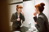 Donna di affari che applica rossetto in bagno hotel — Foto stock