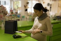 Pregnant woman making payment through mobile phone in store — Stock Photo