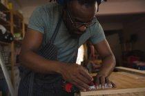 Карпентер вимірювання дерев'яна Планка з рулеткою в майстерні — стокове фото