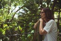 Nachdenkliche Frau lehnt an Tor im Garten — Stockfoto