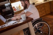 Disabled man noting while using laptop at home — Stock Photo