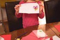 Seção intermediária da menina apresentando carta em casa — Fotografia de Stock