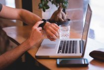 Gros plan de l'homme utilisant smartwatch tout en étant assis avec un ordinateur portable dans un café . — Photo de stock