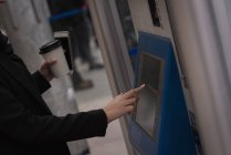 Mid section of woman using ticket machine at railway station — Stock Photo