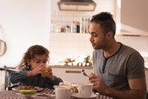 Pai e filha tomando café da manhã na cozinha em casa . — Fotografia de Stock