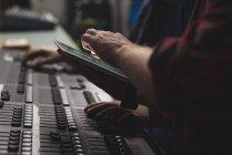 Dos mezcladores de sonido usando tableta digital en estudio . - foto de stock