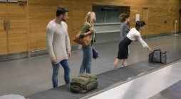 Commuters taking their baggage from baggage carousel at airport — Stock Photo
