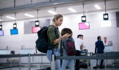 Woman using mobile phone while standing in queue at airport — Stock Photo