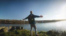 Vista posterior de hombre excursionista de pie con los brazos extendidos en campo - foto de stock