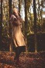Mujer hablando por teléfono móvil en el bosque - foto de stock
