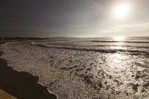 Belo pôr do sol sobre a onda do mar na praia de areia. — Fotografia de Stock