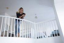 Молода жінка вдома за допомогою мобільного телефону — стокове фото