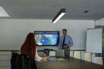 Compañeros de negocios que interactúan entre sí en la reunión en la oficina - foto de stock