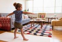 Маленькая девочка выполняет упражнения на растяжку в гостиной на дому — стоковое фото