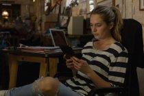 Жіночий механік, використовуючи цифровий планшетний в майстерні — стокове фото
