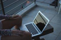 Mujer usando el ordenador portátil en el balcón en casa - foto de stock