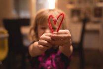 Девочка держит сердце формы украшения дома — стоковое фото