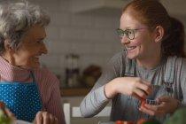 Бабуся і внучка, посміхаючись кухні в домашніх умовах — стокове фото
