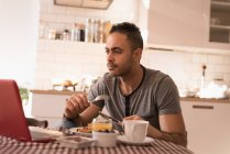 Man having breakfast in kitchen at home. — Stock Photo