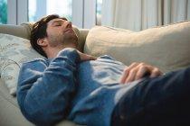 Мужчина спит на диване в гостиной дома — стоковое фото