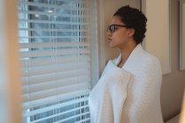 Jeune femme enveloppée dans une couverture regardant par la fenêtre à la maison — Photo de stock